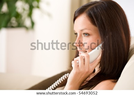On the phone home - woman calling in living room - stock photo