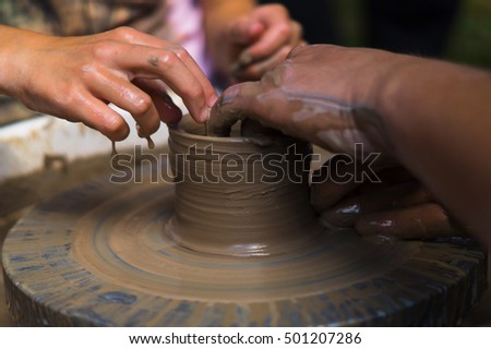 On the potter's wheel pottery blank. One can see the hand of the potter and his assistant that give the product form.