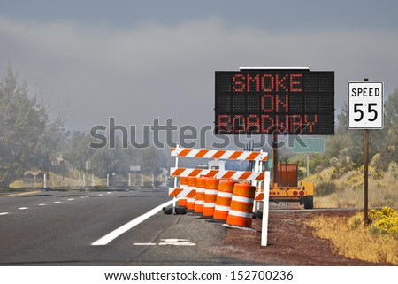 On the road near a forest wildfire the warning signs were put up to warn drivers about the smoke on the roadway. - stock photo