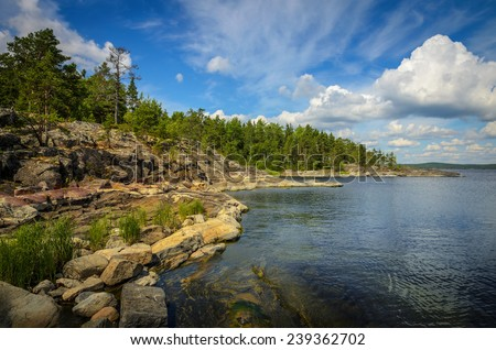 on the rocky shore of the north lake in the fair weather - stock photo