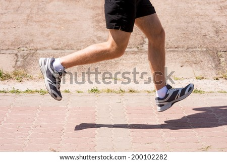 On the run.  Side view close-up image of man running outdoors  - stock photo