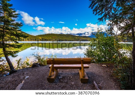 On the shore of lake - comfortable wooden benches. Early morning on cold Pyramid Lake, Jasper National Park - stock photo