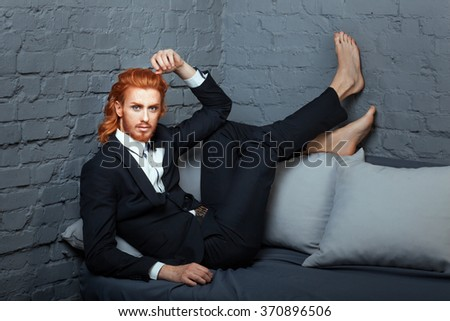 On the sofa is the guy, his legs battened down on it a business suit. On the face of freckles, and color bright red hair. - stock photo