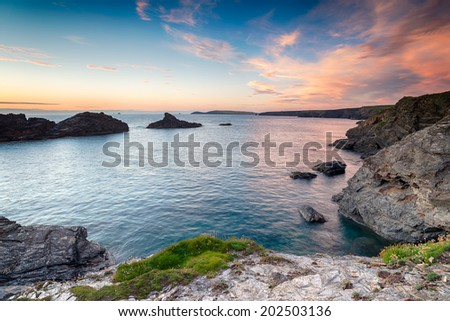 On the south west coast path near Porthcothan between Newquay and Padstow in Cornwall and looking out towards Trevose Head in the far distance - stock photo
