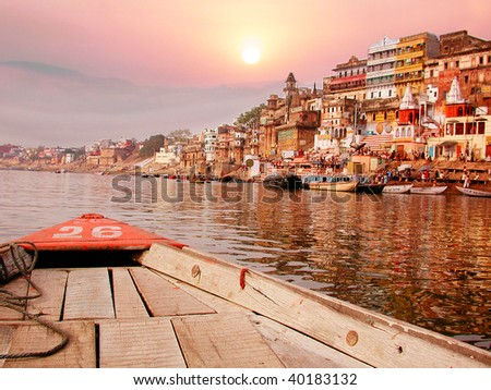 On the sunset river bank on the ganges in India on an old wooden boat.