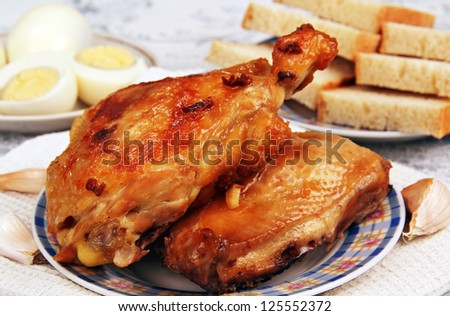 on the table fried chicken on a plate, bread and boiled eggs in the background. - stock photo