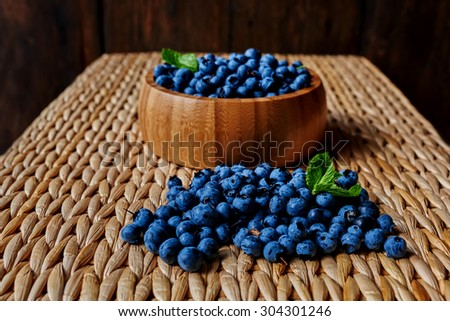 On the table is a light rattan deep wooden plate light wood, which sprinkling fresh ripe blueberries - stock photo