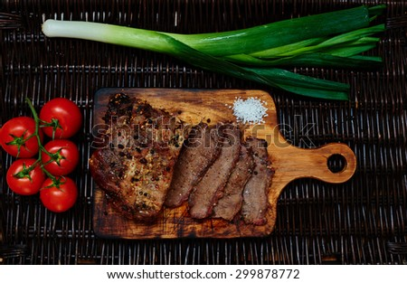 On the table lies a rattan board which served pork tenderloin baked in the oven in one piece, next leeks and cherry tomatoes from which cook fresh light salad - stock photo