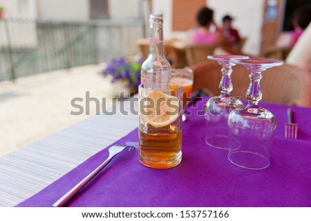 On the table with purple cloth is a beer with lemon in a glass bottle in the background, are on the table cutlery - stock photo