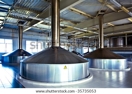 On the territory of brewer's plant with steel fermentation vats - stock photo