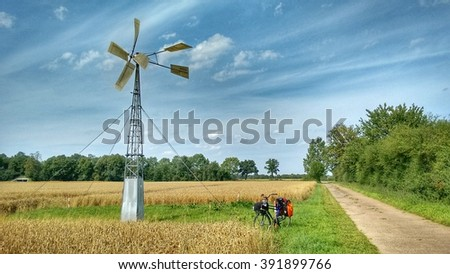 On the way: Bicycle parked at a field between the road and an old wind wheel. Bright blue sky with some clouds, trees and corn meadows are part of the photo. - stock photo