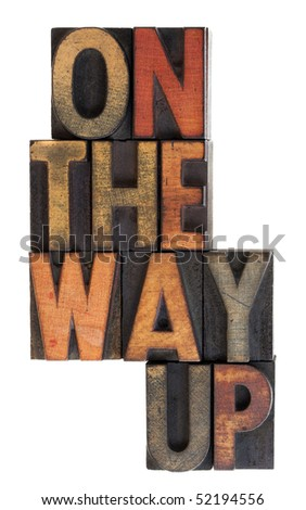 On the way up phrase in vintage letterpress wooden type, stained by ink, vertical layout, isolated on white - stock photo
