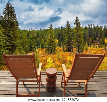 On the wooden platform there are two wicker deck chairs. The lush colorful autumn in the Rocky Mountains of Canada - stock photo