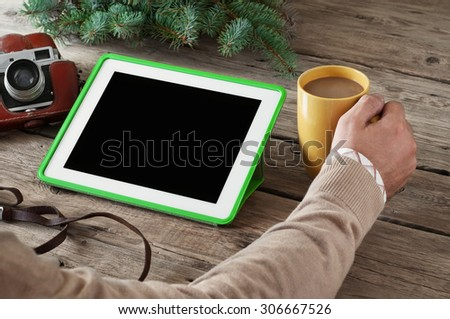 on the wooden table closeup white tablet computer, coffee cup, vintage camera and a sprig of spruce. Copy space. Free space for text - stock photo