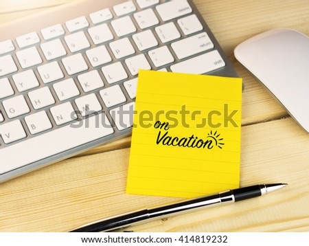 On vacation on sticky note on work table - stock photo