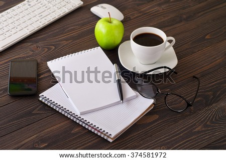 On wooden office desk, stack notepads, smartphone, cup of coffee and money. top view with copy space - stock photo