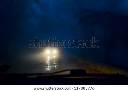 Oncoming cars in the fog on a mountain road. Poor visibility. - stock photo