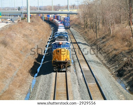 Oncoming freight train rounding a curve with back end of second train - stock photo