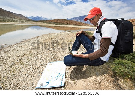 One adult tourist traveller hiker with compass in Himalayas mountains - stock photo