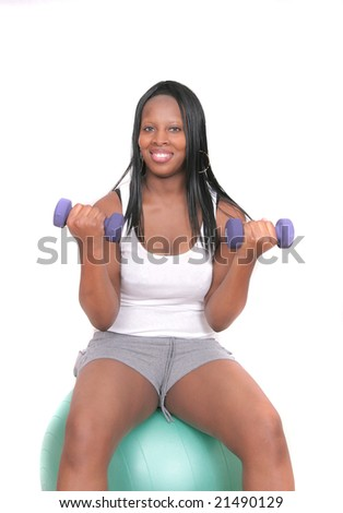 one African American woman working out lifting weights on a physio ball over white - stock photo