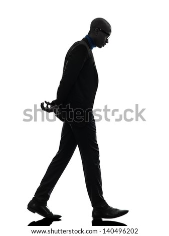 one african  black man walking  looking down   in silhouette studio on white background