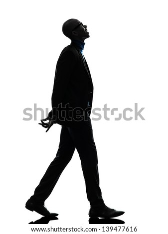 one african  black man walking looking up smiling  in silhouette studio on white background