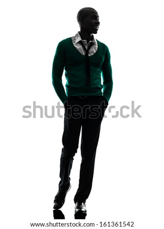 one african  black man walking smiling  in silhouette studio on white background - stock photo