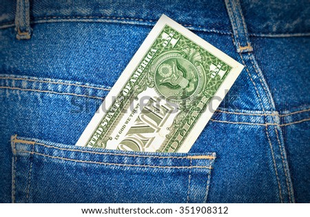 One american dollar sticking out of the jeans pocket