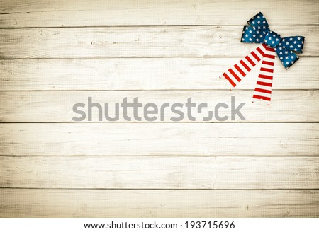 One American Flag Bow in upper right corner on Rustic White or Gray Board Background with room or space for copy, text.   Horizontal with old fashioned, sepia processing. - stock photo
