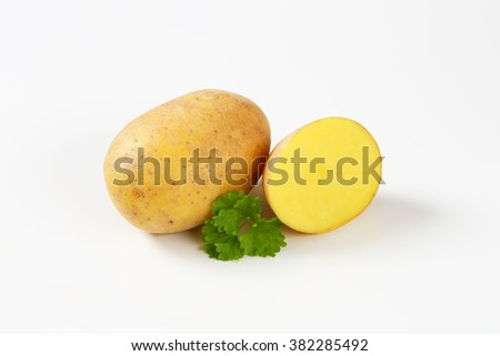 one and half raw potatoes and parsley on white background