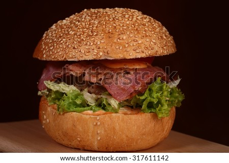 One appetizing big delicious fresh burger with green lettuce red tomato cheese and bacon slice and white bread bun with sesame seeds on black background closeup, horizontal picture - stock photo