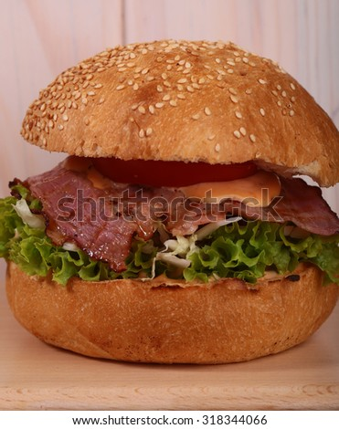 One appetizing big delicious fresh burger with green lettuce red tomato cheese and bacon slice and white bread bun with sesame seeds on wooden background closeup, square picture - stock photo