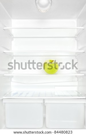 One apple in open empty white refrigerator. Weight loss diet concept. - stock photo