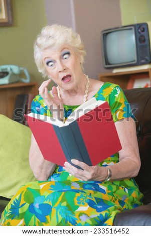 One astonished senior female reading a book - stock photo