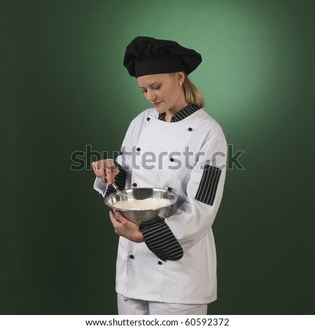 one atractive cook, she is wearing professional uniform and standing stearing a flour bowl.
