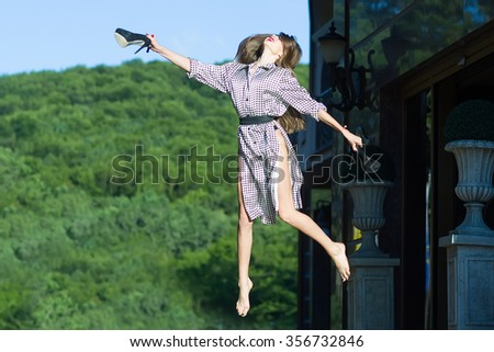One attractive happy jumping smiling young stylish woman with long hair in black and white blouse holding high heeled shoes sunny day outdoor on natural background, horizontal picture - stock photo