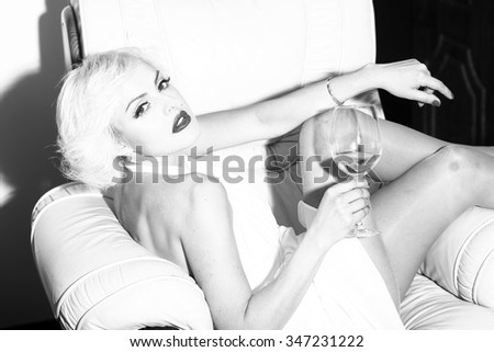 One attractive sensual smiling sexy young retro woman with blonde hair bright lips in dress in monroe style indoor drinking glass of wine sitting in chair black and white, horizontal picture - stock photo