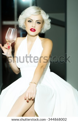One attractive sensual smiling sexy young retro woman with blonde hair bright red lips in white dress in monroe style indoor with glass of wine sitting on chair, vertical picture - stock photo