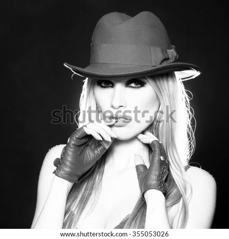 One attractive sexual sensual young blonde woman with long hair in cool cowboy hat gloves and erotic bra as strip dancer black and white, square picture - stock photo