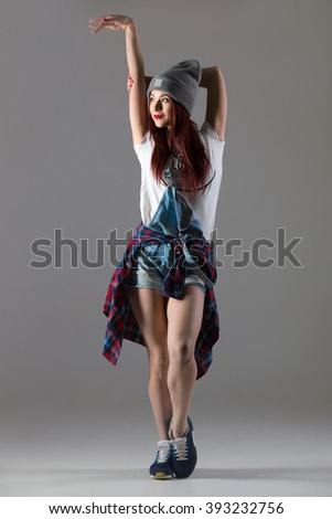 One attractive smiling fit cute young woman in casual clothing warming up, posing. Modern style beautiful dancer working out, stretching, dancing. Full length image on studio gray background - stock photo
