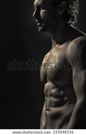 One attractive strong young naked sweat muscular male model with curly hair and beautiful straight body standing in studio on black background, vertical picture - stock photo