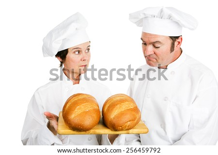 One baker evaluates another baker's fresh Italian bread.  Isolated on white.