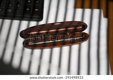 One ball pen in brown wooden case on table with white paper and keyboard and jalousie shade in stripes on office background, horizontal picture - stock photo