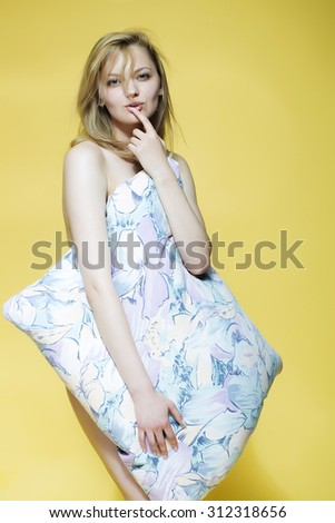 One beautiful playful sexy naked smiling woman with blonde hair holding big pillow in bright flower pattern pillow-case pastel colours standing on yellow studio background, vertical picture - stock photo