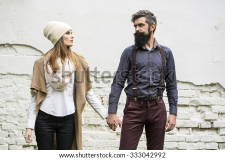 One beautiful stylish emotional couple of young woman and senior man with long black beard standing close to each other outdoor in autumn street on white brick wall background, horizontal picture - stock photo