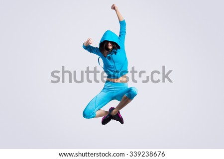 One beautiful young fit modern dancer lady in blue sportswear hoodie sweater working out, dancing and jumping, full length, studio image on gray background - stock photo