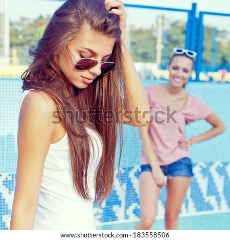 one beautiful young girl is watching the other playing with her gorgeous long hair  - stock photo