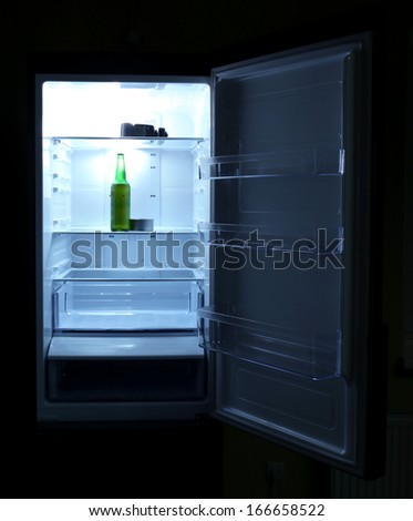 One  beer bottle and canned tune in open empty refrigerator: bachelor fridge concept. - stock photo