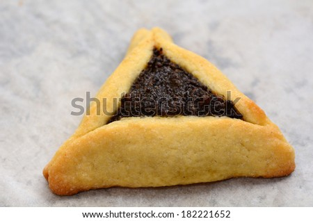 One big backed Hamentashen, Ozen Haman, Purim cookie for the Jewish holiday Purim. Isolated on baking paper. (Copy space) - stock photo