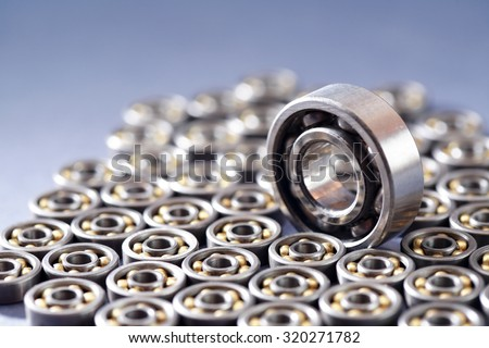 One big ball bearing among lot of small ball bearings - stock photo